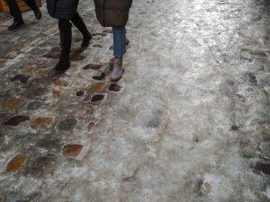 People walk on ice covered sidewalk