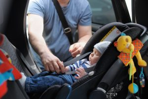 Parent places infant in child car safety seat