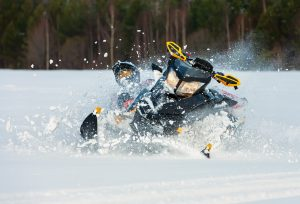 rider falls off as snowmobile crashes