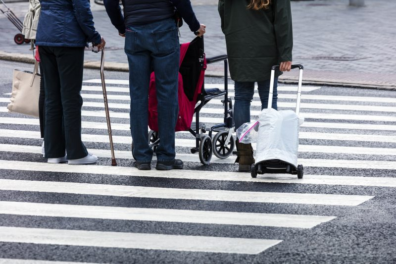 pedestrians with luggage cane and walker cross the street