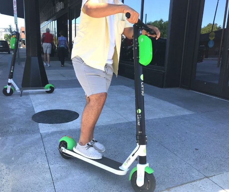 Man Stands on Rental Scooter