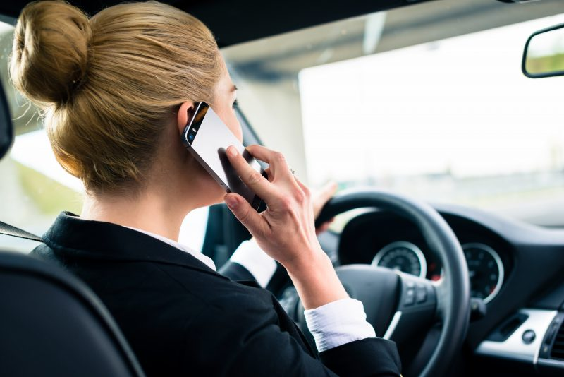 Woman Holds Cell Phone While Driving