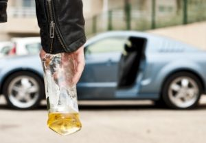 Man carrying a bottle of alcohol toward car