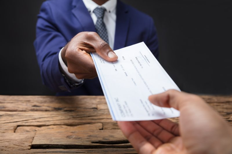 Businessman hands over a check