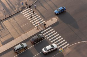 People cross a busy street with a pedestrian island